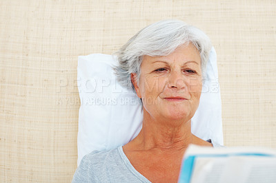 Buy stock photo Closeup of senior woman sitting on bed and reading a novel
