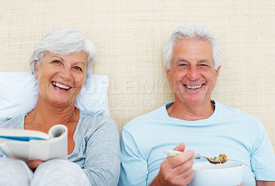 Buy stock photo Senior couple sitting on bed and smiling with man having breakfast