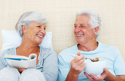 Buy stock photo Senior couple smiling and looking at each other while sitting on bed in the morning