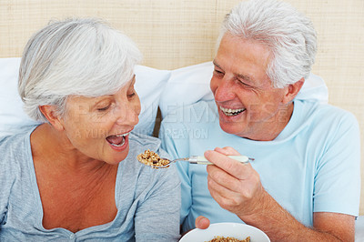 Buy stock photo Closeup of senior couple sitting on bed with man feeding breakfast to woman