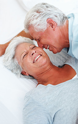 Buy stock photo Senior couple relaxing in bed and having a good time together