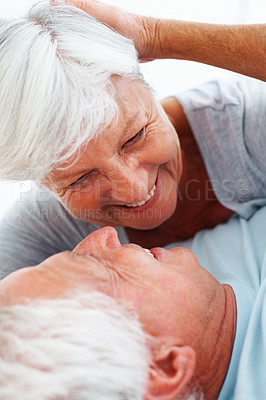 Buy stock photo Closeup of romantic senior couple lying in bed and smiling