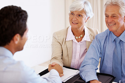 Buy stock photo Portrait of a happy old couple shaking hands with consultant at office