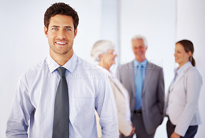 Buy stock photo Portrait of handsome businessman with colleagues discussing in background