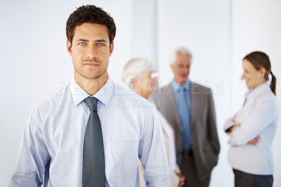 Buy stock photo Portrait of confident businessman with colleagues discussing in background