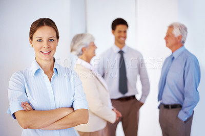 Buy stock photo portrait of pretty young woman with colleagues discussing in background