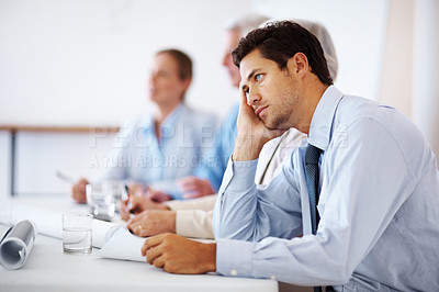 Buy stock photo Portrait of a tired young business man getting bored during seminar at office