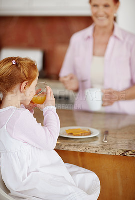 Buy stock photo Portrait of a small girl drinking juice while senior woman in blur background
