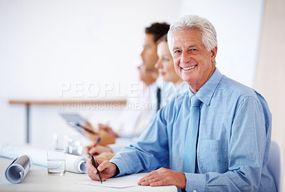 Buy stock photo Portrait of a happy old businessman writing notes in a meeting with colleagues at the back