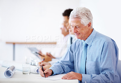 Buy stock photo Portrait of a successful old businessman writing notes during a corporate meeting