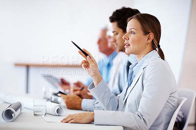 Buy stock photo Female business executive raising pen while sitting amongst colleagues during a corporate meeting