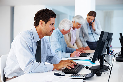 Buy stock photo Smart young businessman working on computer with colleagues in background