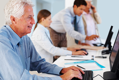 Buy stock photo Mature business man working on a computer with colleagues in the background