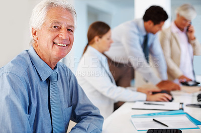 Buy stock photo Portrait of smiling senior executive sitting at his desk with colleagues working in background
