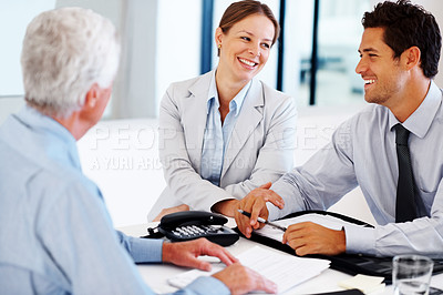Buy stock photo Portrait of a happy young couple talking with a consultant and signing a contract paper