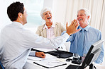 Happy couple giving high five to a advisor during a meeting