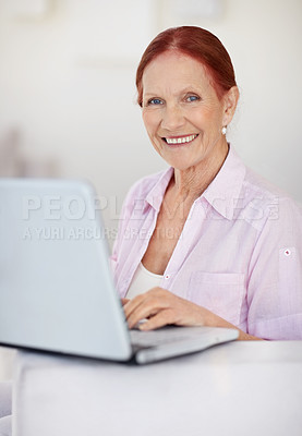 Buy stock photo Portrait of a smiling mature woman working on a laptop