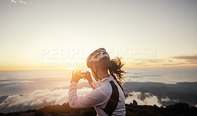 Buy stock photo Cropped shot of a young woman taking a photo while cycling in the mountains
