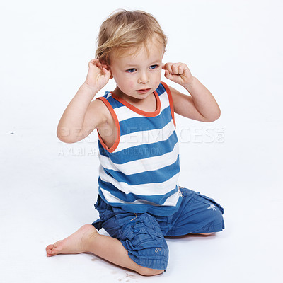 Buy stock photo Portrait of a cute little boy sitting on floor and looking away over white background