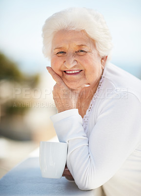 Buy stock photo Portrait of a happy senior woman standing outside and holding a cup of coffee