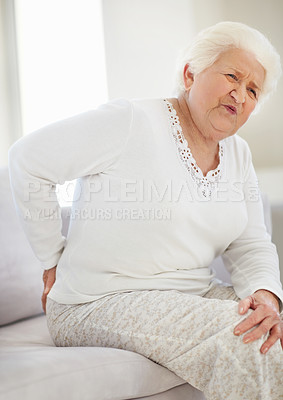 Buy stock photo Shot of a senior woman wincing from lower back pain