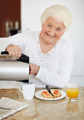 Buy stock photo Portrait of a happy elderly woman pouring coffee in cup while having breakfast