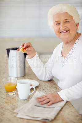 Buy stock photo Portrait of a happy elderly woman having breakfast and reading the paper