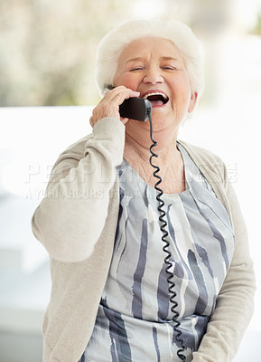 Buy stock photo Shot of a happy senior woman laughing while talking on the phone