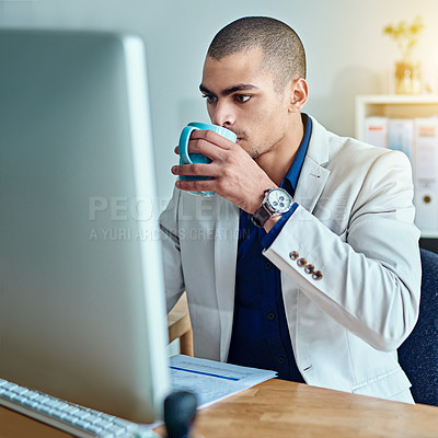 Buy stock photo Cropped shot of a young businessman drinking coffee while working in an office