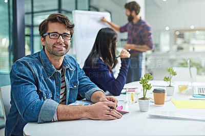 Buy stock photo Portrait of a young businessman sitting in a meeting with colleagues in the background