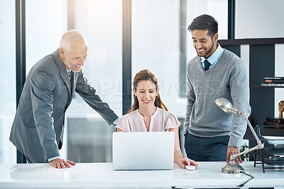 Buy stock photo Cropped shot of three businesspeople using a laptop in the office