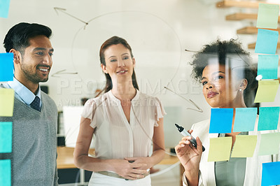 Buy stock photo Shot of a group of young colleagues having a brainstorming session at work