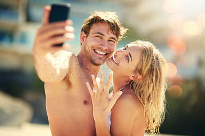 Buy stock photo Cropped shot of a young woman showing off her wedding ring while taking a selfie with her husband