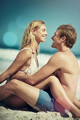 Buy stock photo Cropped shot of an affectionate young couple sitting face to face on the beach