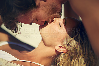 Buy stock photo Cropped shot of a young couple kissing on the beach