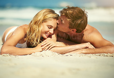 Buy stock photo Cropped shot of an affectionate young couple lying on the beach
