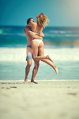 Buy stock photo Full length shot of an affectionate young couple embracing on the beach