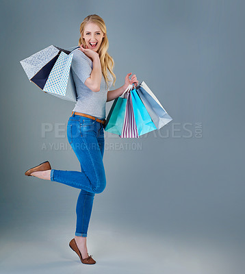 Buy stock photo Full lenghth studio shot of a happy young woman holding up a selection of shopping bags