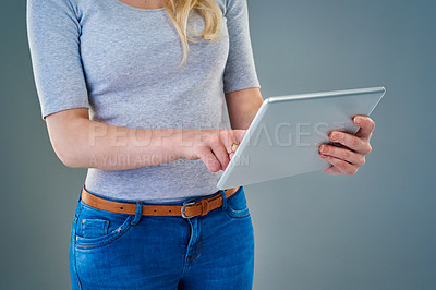 Buy stock photo Cropped studio shot of a young woman using her tablet