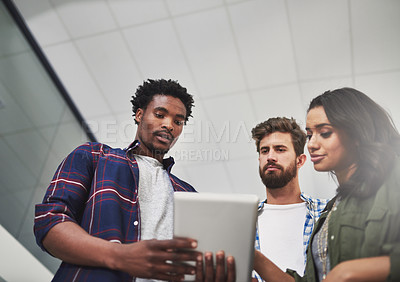 Buy stock photo Cropped shot of three young designers working on a digital tablet in a modern office