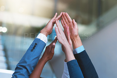 Buy stock photo Cropped shot of a group of people putting their hands up together in unity