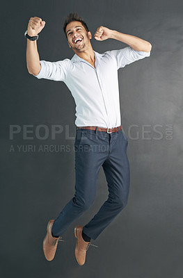 Buy stock photo Studio shot of a happy businessman jumping for joy