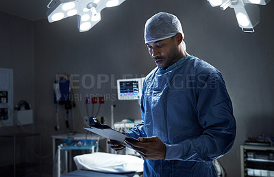 Buy stock photo Shot of a surgeon looking at a patient's file in an operating room
