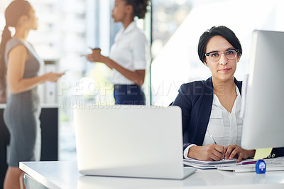 Buy stock photo Cropped portrait of a businesswoman working in her office with colleagues in the background