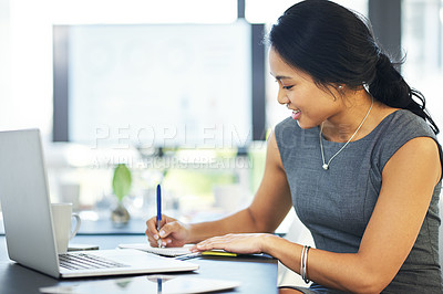 Buy stock photo Cropped shot of a young businesswoman writing notes while working on a laptop in a modern office