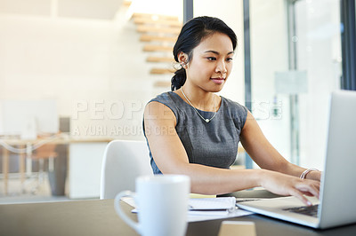 Buy stock photo Cropped shot of a young businesswoman working on a laptop in a modern office