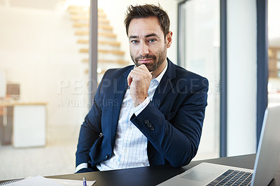 Buy stock photo Portrait of a businessman working on a laptop in a modern office