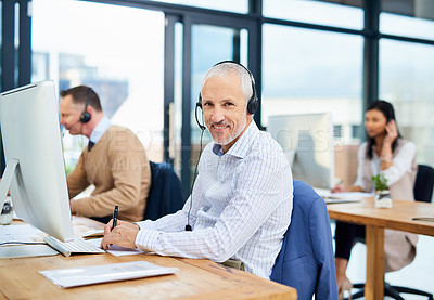 Buy stock photo Cropped portrait of a mature businessman working in his office with colleagues in the background