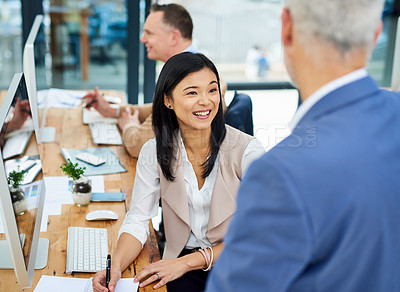 Buy stock photo Cropped shot of two businesspeople working together in the office with a colleague in the background