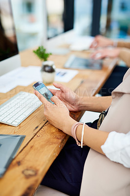 Buy stock photo Cropped shot of an unrecognizable businesswoman sending a text message while sitting in the office